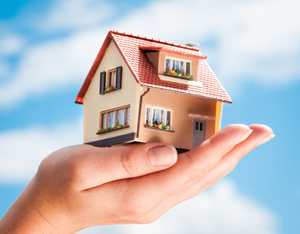 House in the hands of the man on a background of blue sky